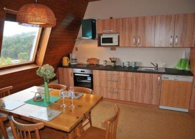 pohled na vybavenou kuchynskou linku a jidelni stul v apartmanu bella vista